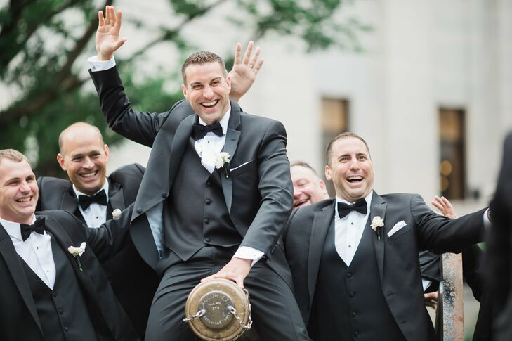 The groomsmen all wore black Vera Wang tuxedos with black vests and bow ties and white ranunculus flowers with handmade bullet cuff links, which reflect Ryan's job.
