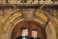 As lovers of wine, Andrew (left) and Kevin decided to wed at Sunstone Winery in Santa Ynez, California. The Tuscan-style venue inspired the neutral, m