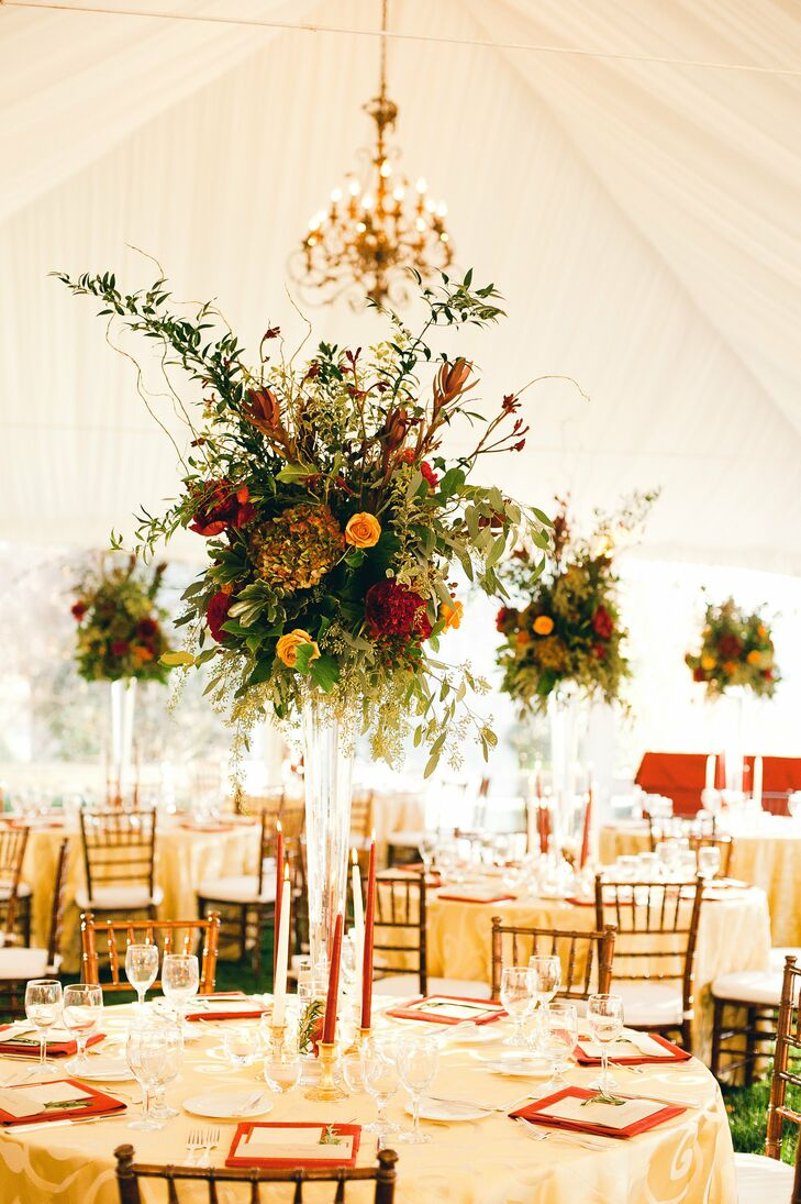 For a rustic-yet-elegant look, Ellie and Adam's florist filled tall clear glass vases with a mix of red and orange roses accented by textured elements like eucalyptus, willow branches, hydrangeas and various greenery.