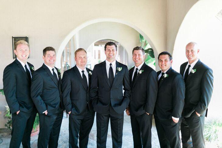 Greg and his six groomsmen wore traditional black suits with polished black loafers and crisp white shirts. They also wore delicate white rosette boutonnieres.