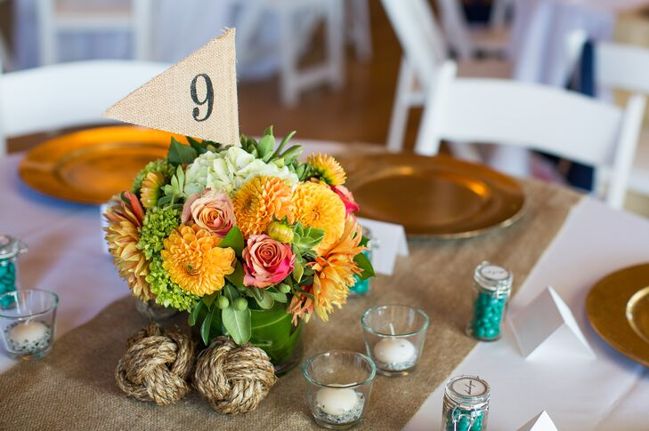 Burlap flag numbers marked each dining table at the reception at Corinthian Yacht Club in Tiburon, California, matching the burlap runners. The flags stuck out from flower centerpieces, filled with bright orange, pink and green flowers.