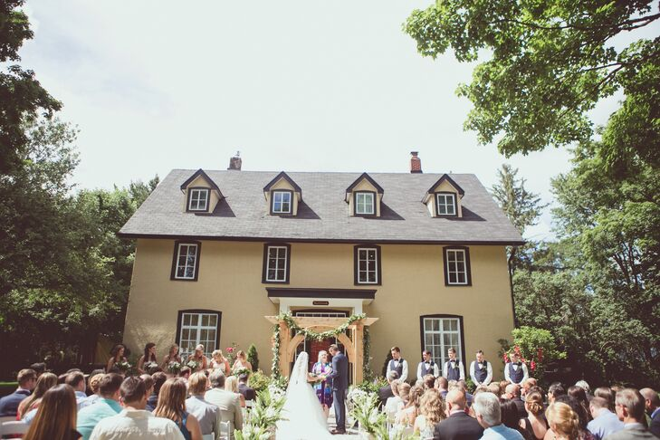 """The wedding ceremony was held on the lawn at Northbrook Farm in Orillia, Ontario, with the aisle located directly in front of the farmhouse. """"Michael fell in love with the house instantly,"""" Kelly-Ann says. """"As he is extremely handy, he hollowed out the large birch stumps for the foxglove flowers and ferns that went inside each one. """"He also made the gorgeous arbor, which we got married under."""" The couple had a 25-minute ceremony with traditions like a unity-candle ceremony."""