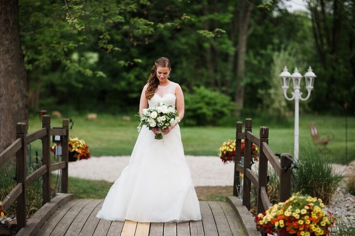 """Caitlin's look was all about sophistication and romance. She visited Julian Gold Bridal in Austin, Texas, with her mother and was instantly won over by the Christos's Annabelle gown, a striking A-line number with an illusion bateau neckline, silk organza skirt and embroidered Chantilly lace detailing. """"The dress made me feel so elegant and feminine,"""" Caitlin says. She kept her accessories simple, pairing the gown with Nadri crystal drop earrings and her mother's cathedral-length veil."""