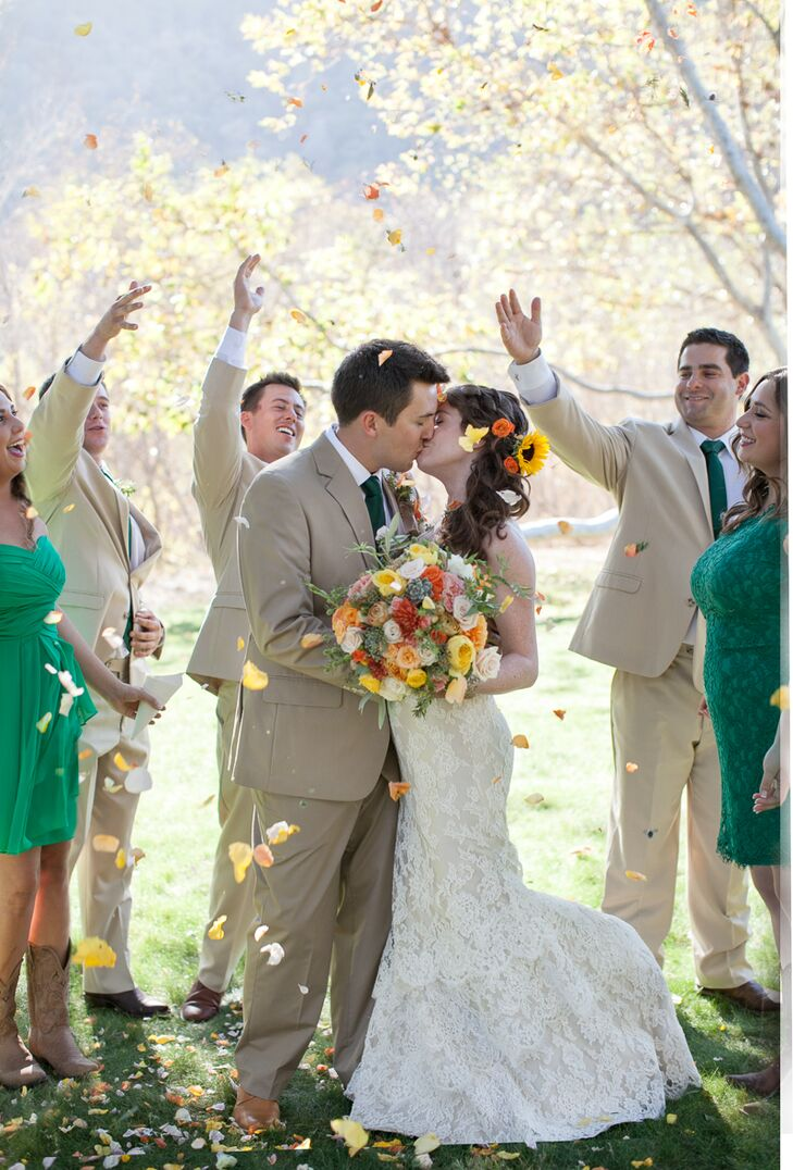Nicole and Bentley kissed as they were surrounded by their wedding party outside at Gardener Ranch in Carmel Valley, California. Bridesmaids wore knee-length dresses in emerald green with vintage brown cowboy boots, while the groomsmen wore khaki-colored suits with emerald green ties that matched the bridesmaid attire.