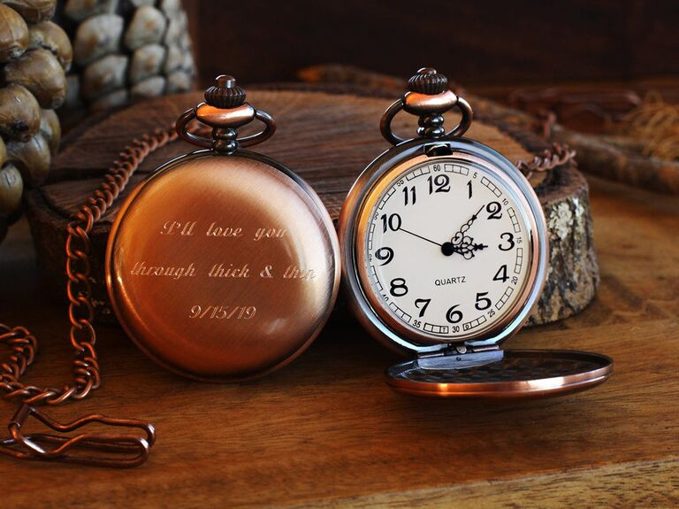 Engraved copper-tone pocket watches shown side by side, one opened and one closed