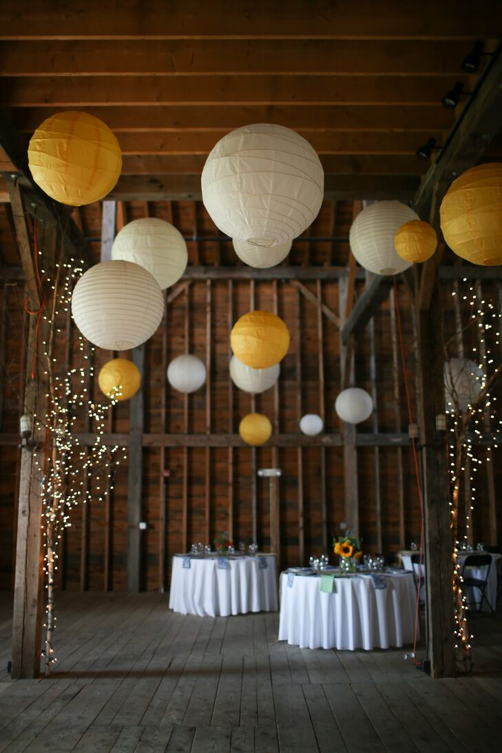 Paper lanterns in different shades of yellow gave the rustic barn space a bright pop of color.