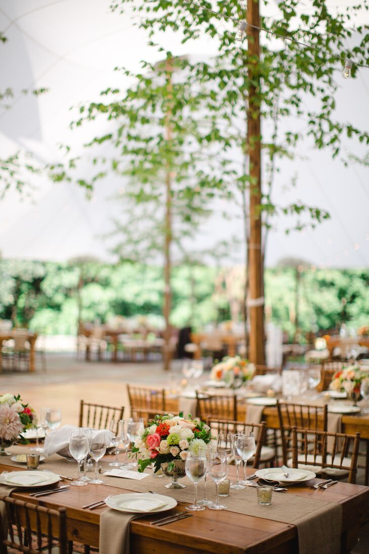 Hannah and Ed made guests feel at home with quaint details like wooden farm tables and burlap linens that exuded warmth, ambiance and family-dinner vibes. Pops of coral in bountiful arrangements of roses, gerbera daisies, dahlias and hydrangeas added a hint of vibrancy to the tablescapes, while votive candles established a feeling of romance and intimacy.