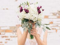 Bride holding an ivory and burgundy bouquet over her face