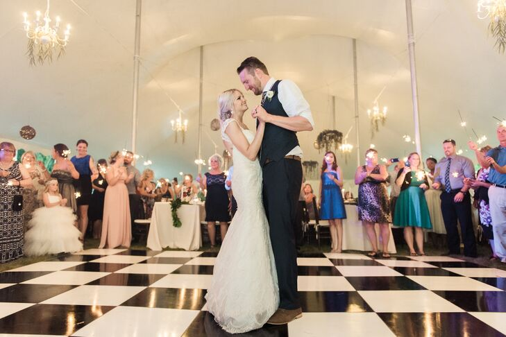 "The couple's first dance was to ""I Don't Dance"" by Lee Brice. Guests waved sparklers around the perimeter of the dance floor."