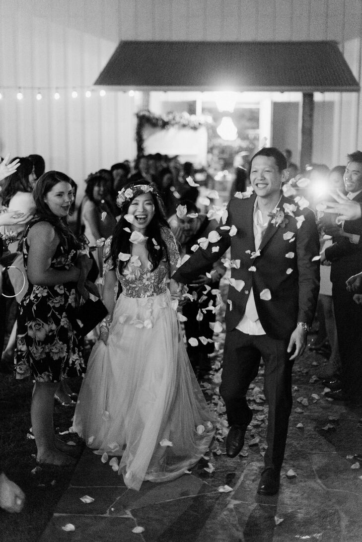 """The newlyweds ended the night walking through a shower of petals, honoring the day's theme, """"Love in bloom."""""""