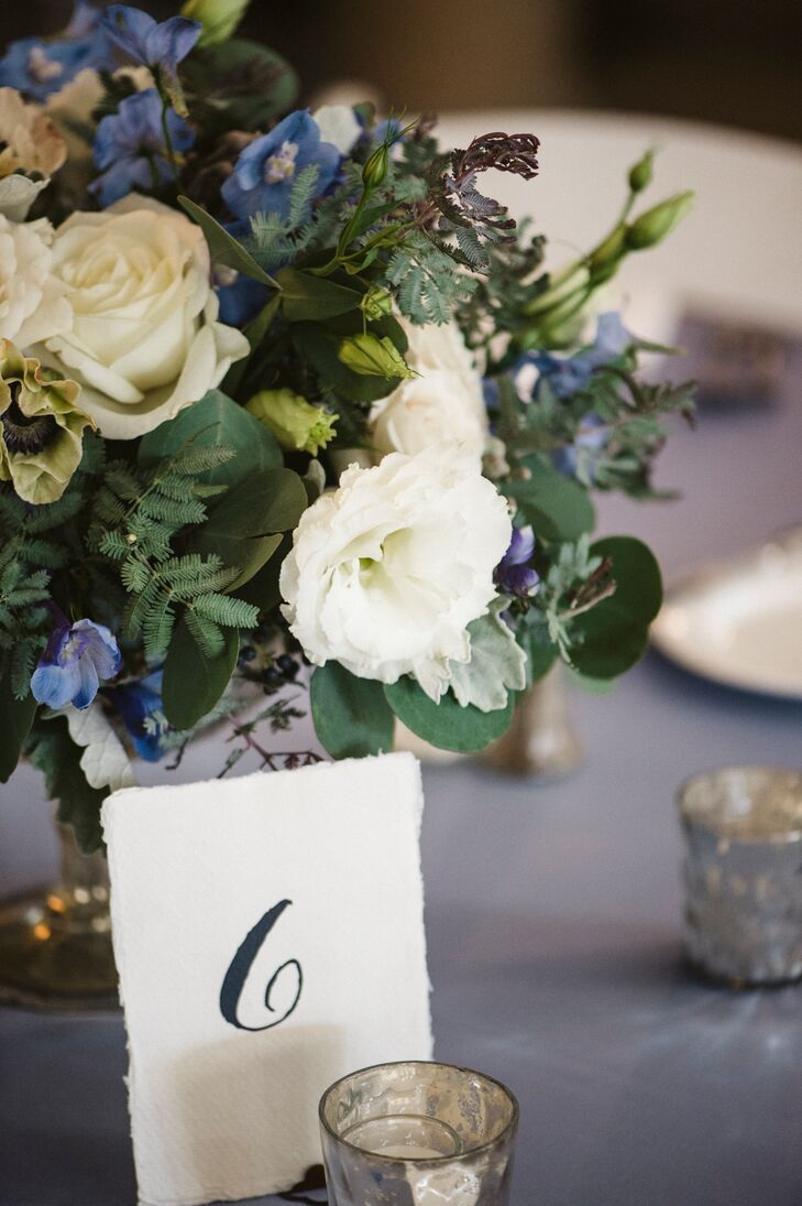 One of centerpieces was a blue and white floral arrangement, including delphinium in varying shades, white miniature spray roses, white lisianthus, blue viburnum berries, silver brunia berries, white anemones and white roses accented with dusty miller and seeded eucalyptus foliages, with five silver mercury-glass votive candles placed around the vase.