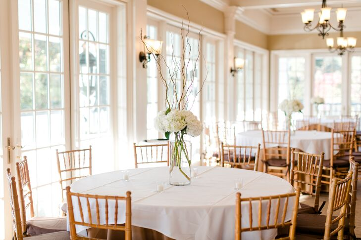 Tall glass vases with ivory hydrangeas and willow branches rested on the center of each table at the reception. The minimal centerpiece embodied a look that was simple, classic, and Southern.