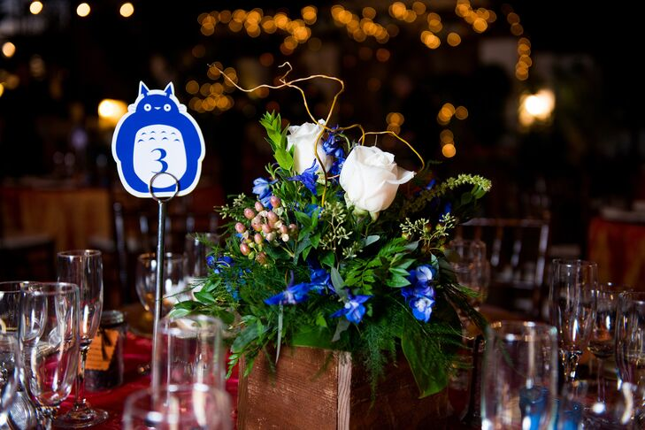 The centerpieces for the tables included arrangements of blue delphinium, white roses, hypericum berries and curly willow with whimsical Totoro table numbers.