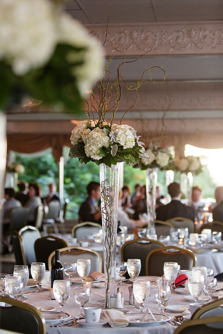 Tall, glass vases were filled with white hydrangea bouquets for dramatic and elegant centerpieces.
