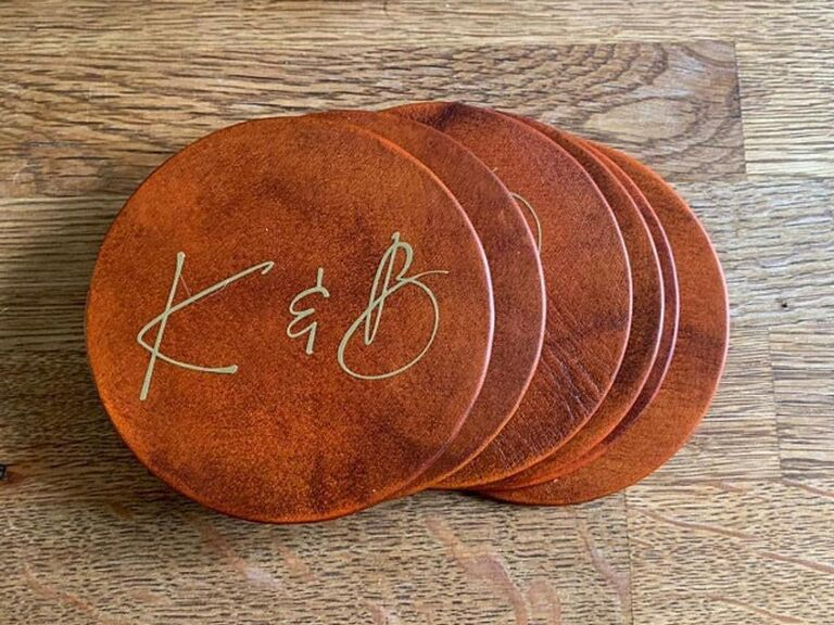 Brown leather coasters stacked with K & B initials in gold