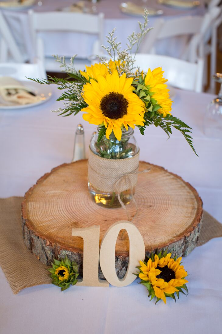 Glass mason jars wrapped with burlap sat on top of large wooden slabs, filled with bright yellow sunflower arrangements that added a pop of color. Rustic table numbers accented with smaller sunflowers leaned against the wooden slab, leading guests to the right table.