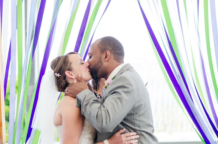 Melanie and Michael were married by a backdrop consisting of purple, blue and green streamers.