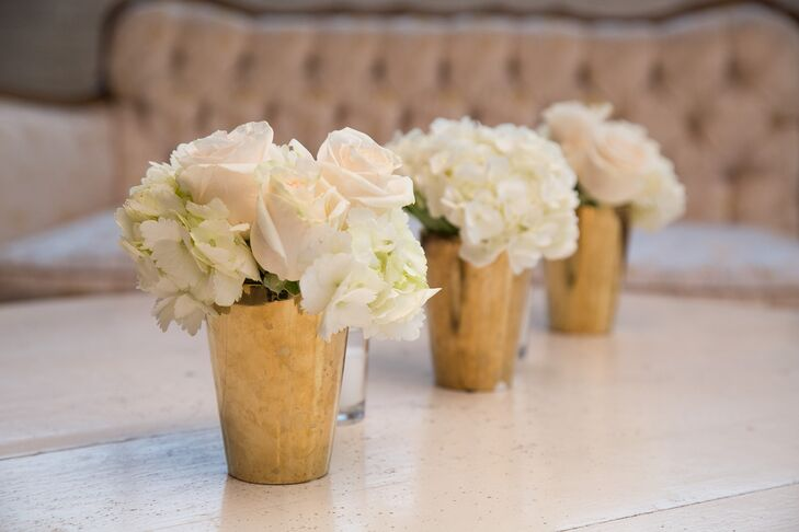 Gold vases filled with ivory roses and hydrangeas added a pop of color to the venue's long dining tables.