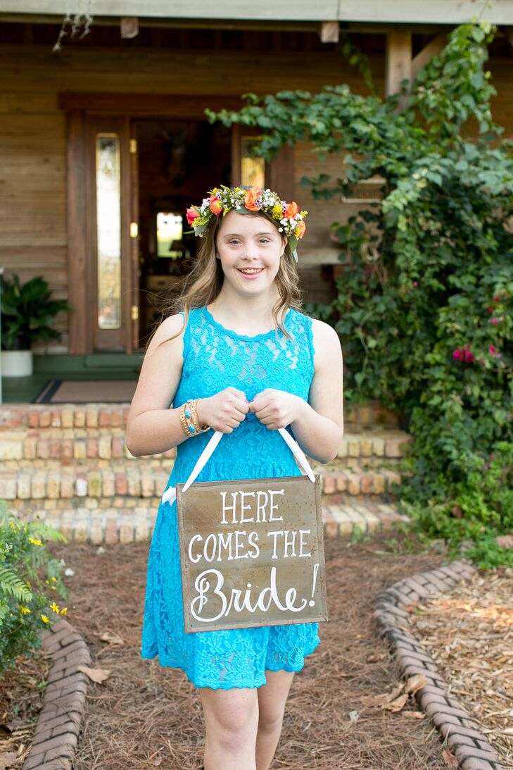 For an even more sentimental touch, their family friend served as the flower girl. She stood out from the bridesmaids in a bright blue lace dress with an illusion neckline. Instead of dropping flowers down the aisle, she wore this organic flower crown lined with coral roses and carried a metal sign.