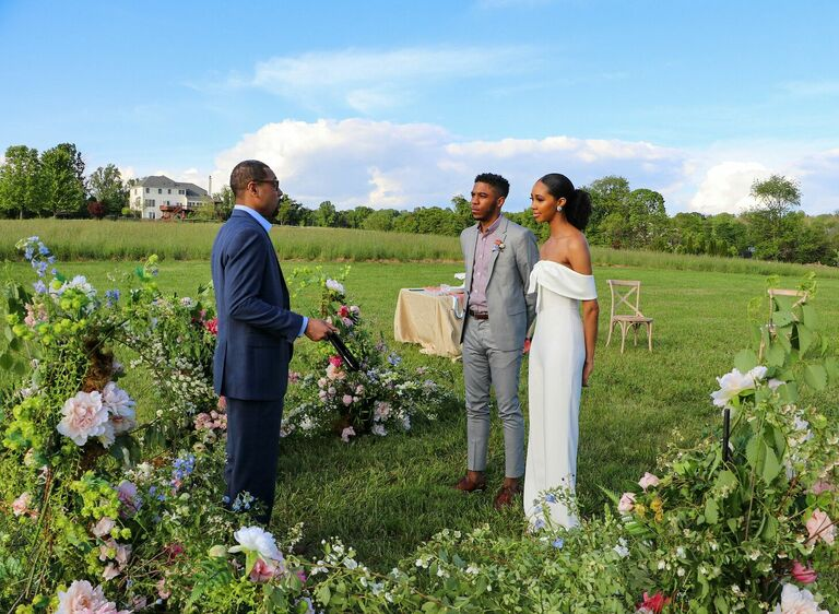 Couple exchanging vows in the middle of a field of flowers