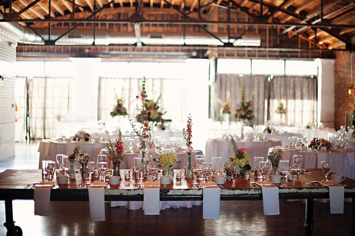 Since the event space at The Guild is big and open, the couple had a blank canvas to create their vision. They combined a distressed wood table with smaller round tables covered in crisp linens and alternated tall, lush centerpieces with shorter, more minimal ones for a modern, eclectic look.