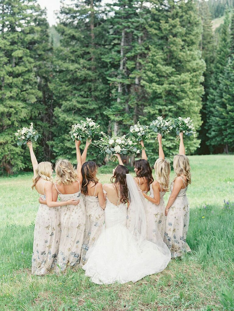 Photo of bridesmaids and bride holding bouquets in the air outside