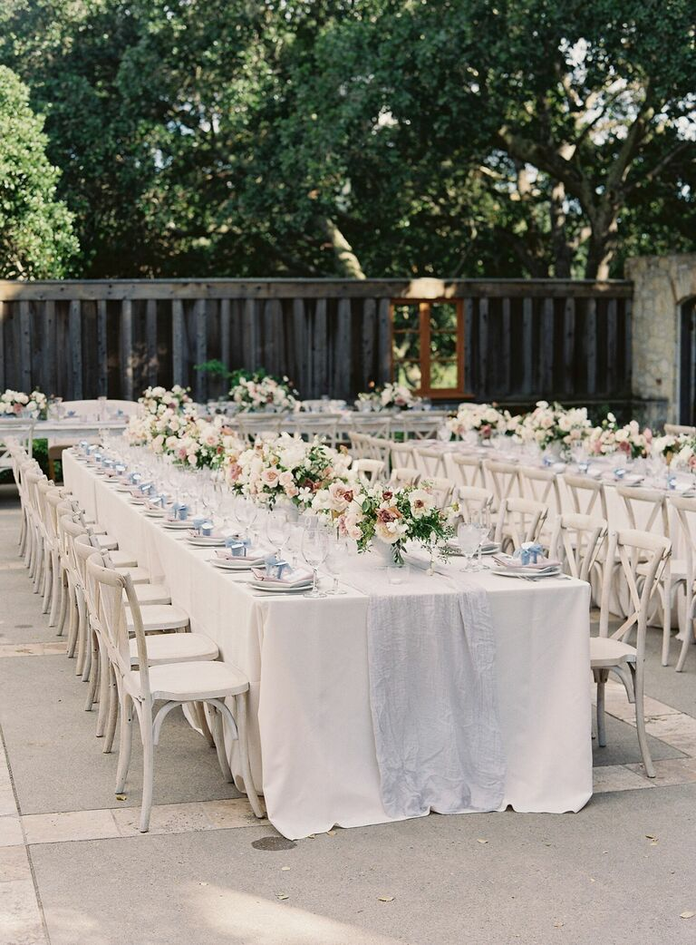 Long reception tables with white linens and white cross-back chairs