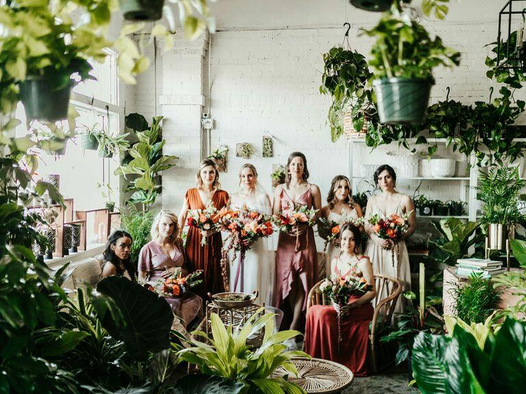 Bridesmaids posing in tree nursery with bride