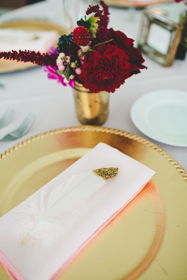 White feathers, dipped in gold glitter, were tucked into the napkins that rested atop gold chargers.