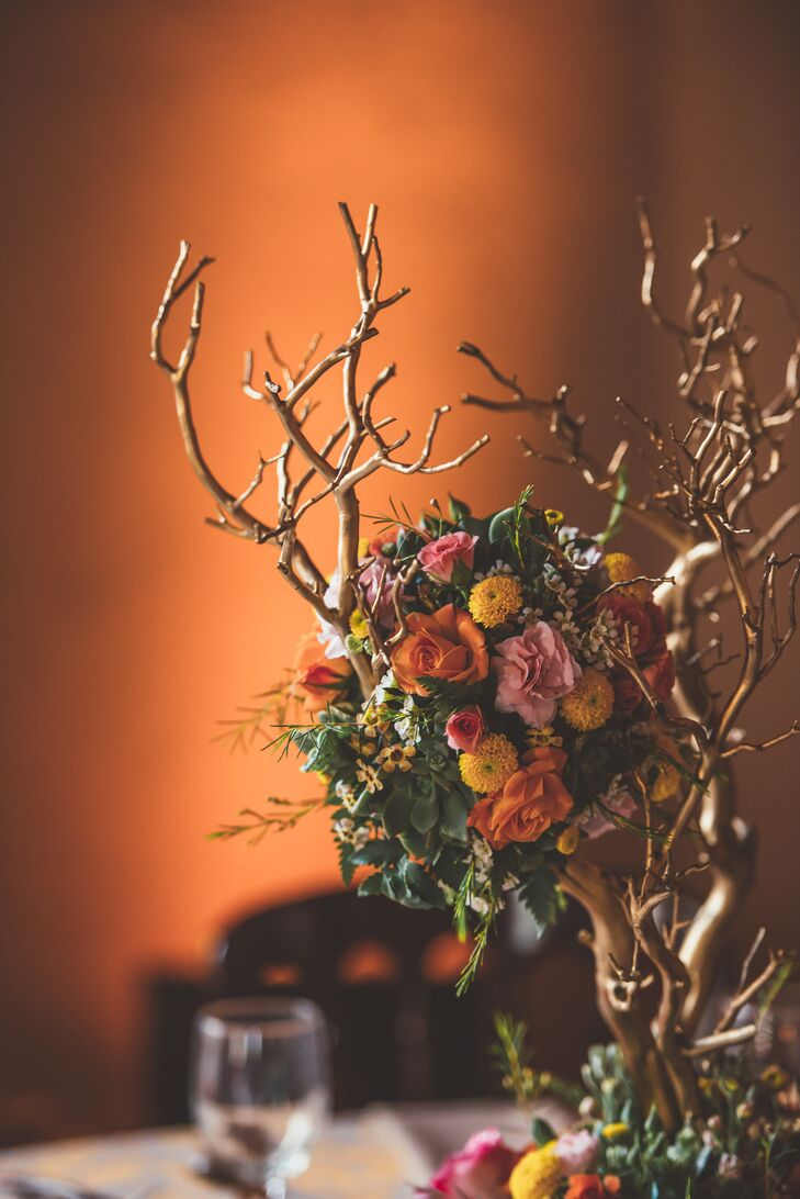 Flower arrangements filled with orange and pink roses, yellow dahlias and green succulents hung from branches and served as centerpieces on dining tables.