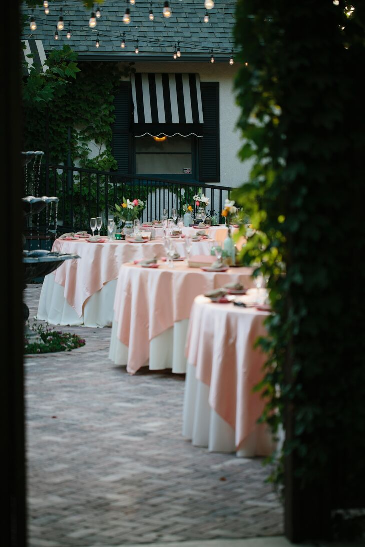 The reception took place outside on the patio at Randall House in Bakersfield, California, where guests sat at round dining tables with white and pink layered linens. Katie arranged the flower centerpieces the morning of the wedding, placed inside mason jars she had collected.