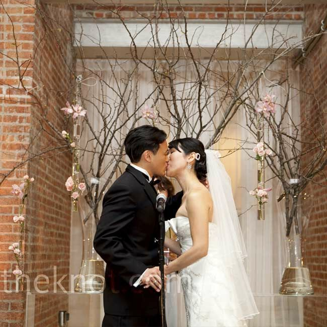 Cherry blossom branches in tall glass vases provided the backdrop for the ceremony.