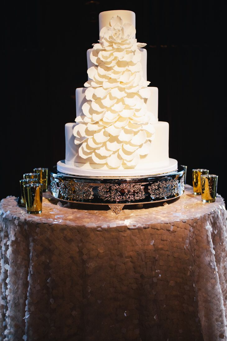 The three-tiered ivory wedding cake was decorated from top to bottom with a ruffled design. The cake was positioned on top of a glamorous gold and black stand.