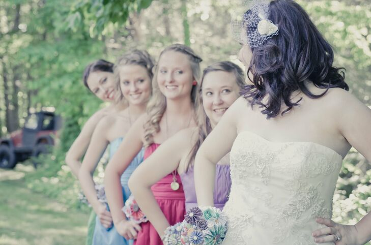 Megan's bridesmaids wore strapless dresses in different jewel tones of purple, dark pink, blue or green, all colors that matched the hue of Megan's DIY bouquet.