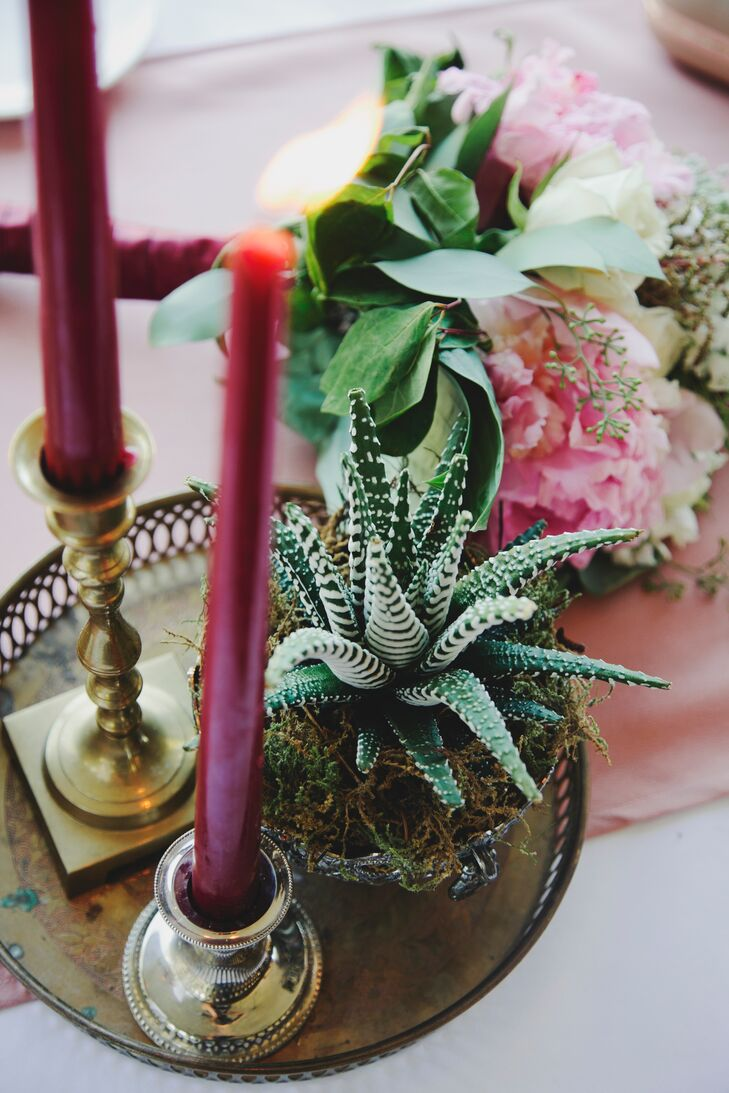 Some of the centerpieces included burgundy candles on gold candlesticks alongside succulents on vintage trays.