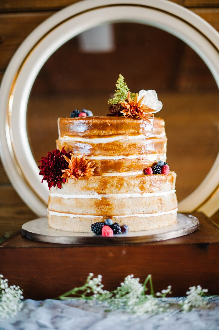 """With some help from Olympia Catering & Events, their wedding cake also achieved a natural look. The two-tier spice cake was separated by cream cheese icing and glazed in caramel, giving it a rich golden color. """"It was the best cake I've ever had,"""" Shelby says. """"Everyone agreed."""" Burgundy and orange dahlias, as well as berries, white lisianthus and greenery decorated each layer."""