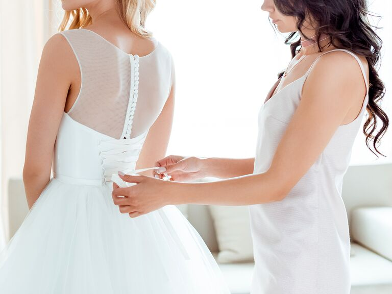 Woman Helping Bride Put On Wedding Dress