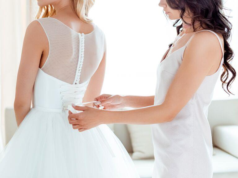 Woman helping bride put on wedding dress