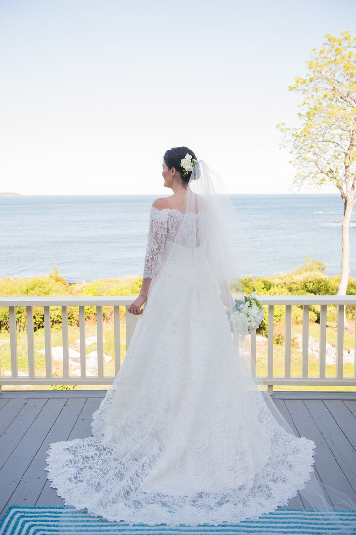 "Sarah's off-the-shoulder Carolina Herrera gown featured delicate lace detailing along the neckline, illusion back and sleeves. The lace continued throughout the skirt and train. ""I am a very classic person, so I knew I wanted a classic and sophisticated look,"" she says."