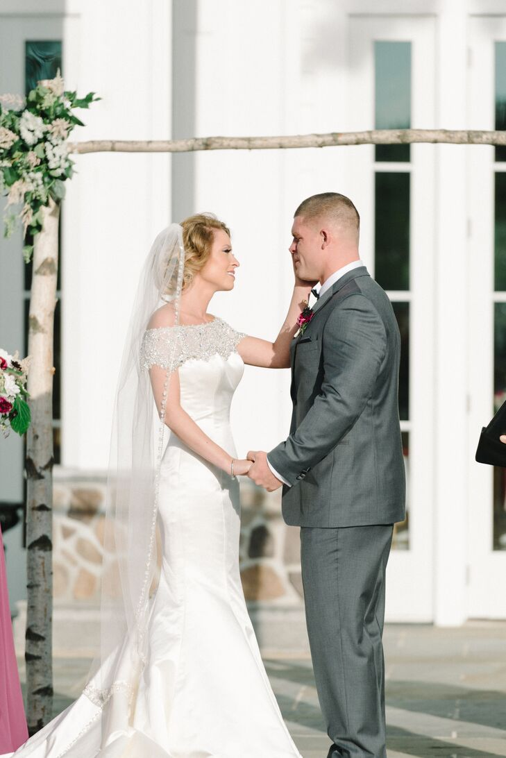 """Surrounding trees along Ryland Inn's garden patio set the scene for the sweet outdoor ceremony in Whitehouse Station, New Jersey. """"It was so emotional,"""" Sarah says. """"My husband cried as I came down the aisle, which was such an unexpected yet sweet moment. It brought the house to tears."""" A birchwood arch from Anna Rose Floral and Event Design framed the entire service, matching their setting. Bunches of classic white Queen Anne's lace, pink astilbes and greenery accented each corner. (The same flowers also appeared in their bouquets and the groomsmen boutonnieres.)"""