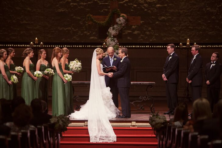 """Lucy and Will said """"I do"""" at Christ Chapel Bible Church with candles glowing in the backdrop. A large wooden cross, covered in a floral garland of green and white hydrangeas and roses, stood on a wooden table behind them."""