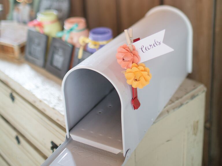 gray wedding card mailbox with pink and orange flower flag on wedding reception table