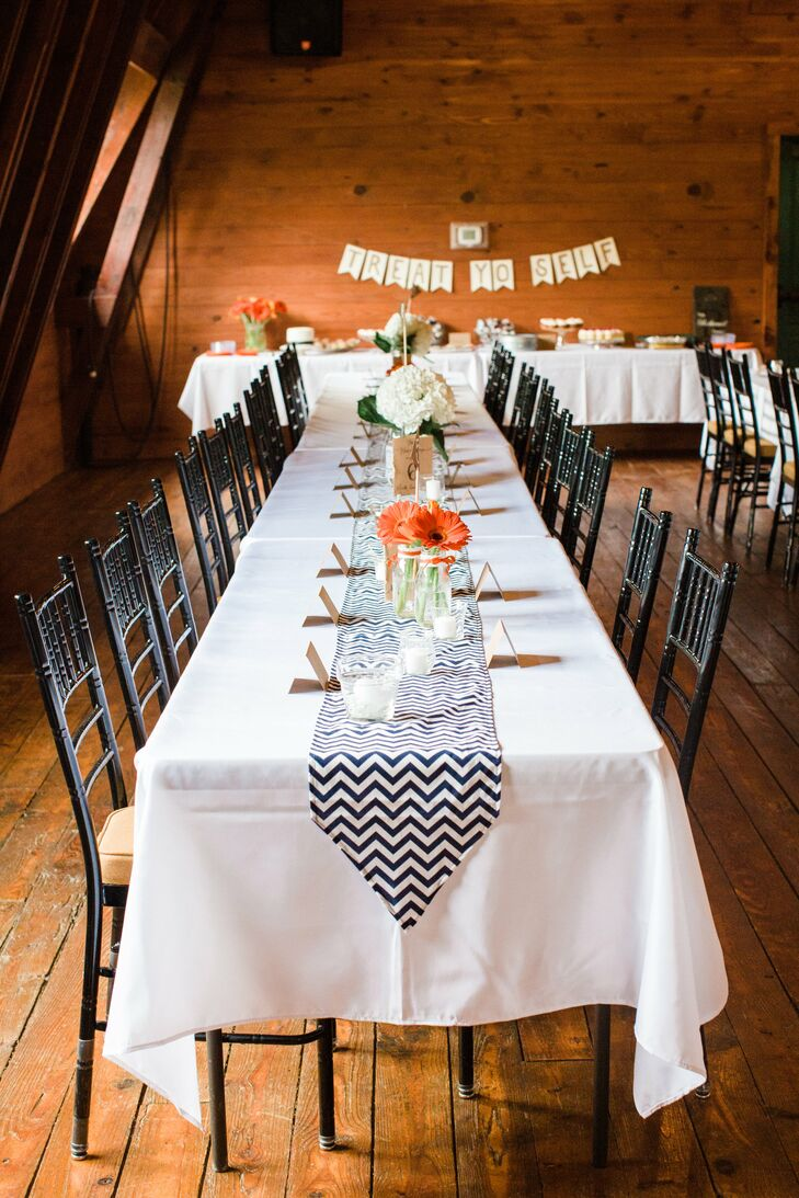 "For the couple's barn reception, tables were topped with an eclectic array of vases and jars, blooms, votive candles, and navy-and-white chevron table runners sewed by the Blair's mother. ""We were lucky that it didn't take much to decorate such a fantastic location,"" Blair says."