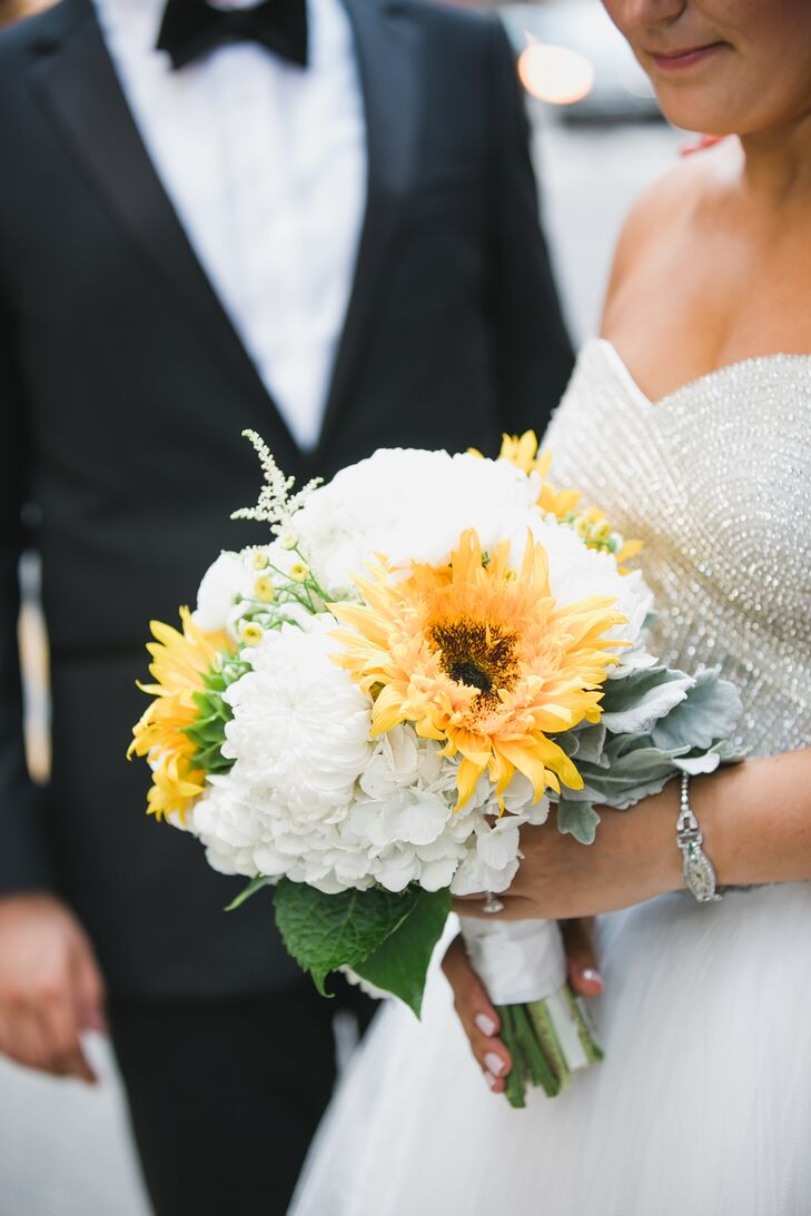 Alyse's bouquet fused classic, rustic and glam styles with a mix of fresh white hydrangeas, vibrant sunflowers, cool blue dusty miller and playful crystal accents.