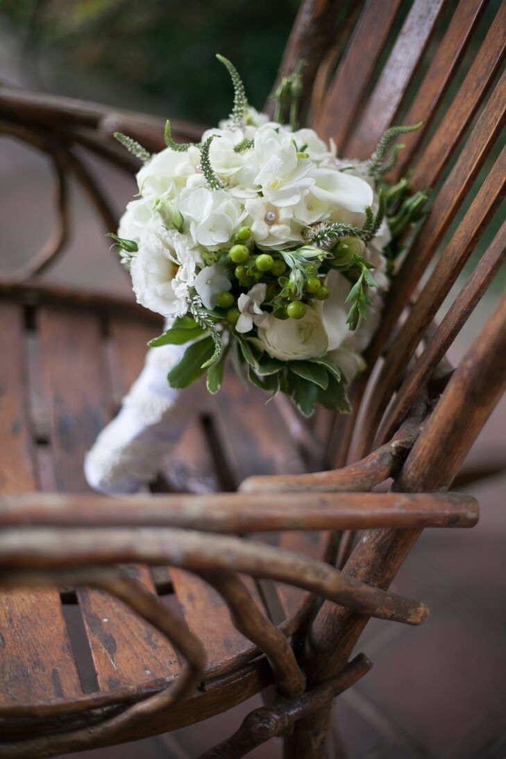 """""""None of our flower choices were sentimental; we just liked the white and green aesthetic,"""" Cam says. The pros at Redshaw Flower Shop filled her bouquet with all-white calla lilies, hydrangeas, lisianthus, ranunculus and veronica. Bunches of green hypericum berries and leaves added some texture to the mix. To make the arrangement a bit more personal, Cam had each stem wrapped in her great-grandmother's lace."""