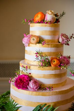 Round Tiered Cake with White and Gold Striped Icing and Colorful Cake Flowers