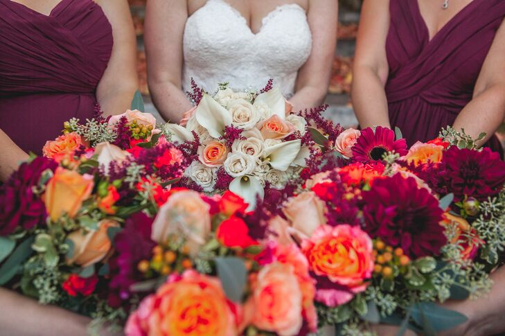 Drawing on the season for inspiration, Anne's Florals & Gifts created striking arrangements filled with rich autumnal hues for the bouquets and boutonnieres. While Sarah's bouquet had a classic feel with blush roses and ivory calla lilies, the bridesmaids' bouquets featured a fresh mix of playful blooms like dahlias, Gerbera daisies, roses and hypericum in shades of fiery orange, deep burgundy and playful peach.