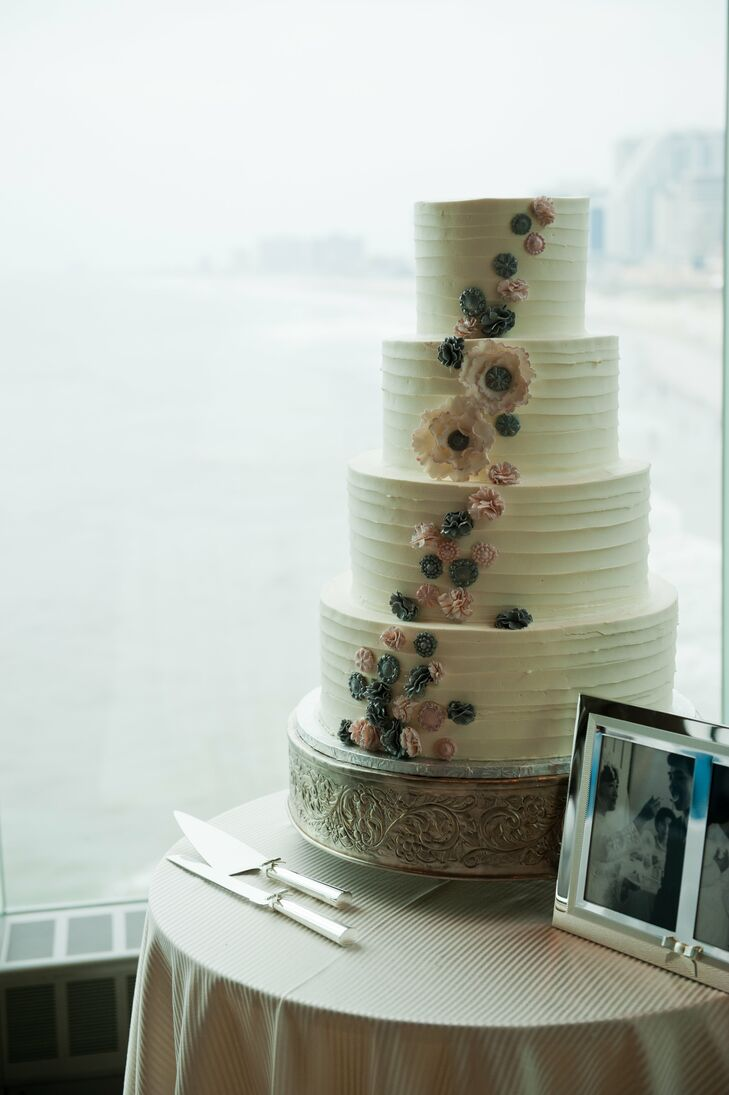 On the wedding day, Kim's sister decorated the four-tier buttercream cake with pink and gray gum paste flowers.