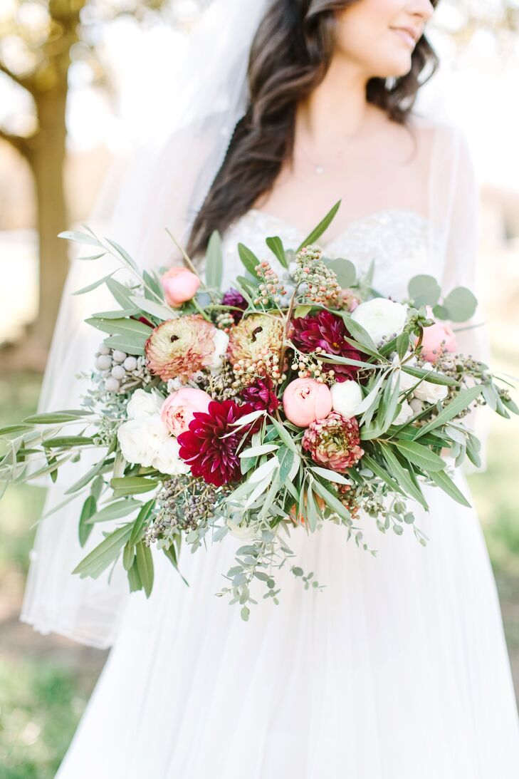 Lydia achieved the look of her bouquet, which perfectly fit the rustic, outdoor wedding with berries,  spray roses, antique rose pompon, ranunculus, white silver dollar eucalyptus, olive branches and bay laurel.
