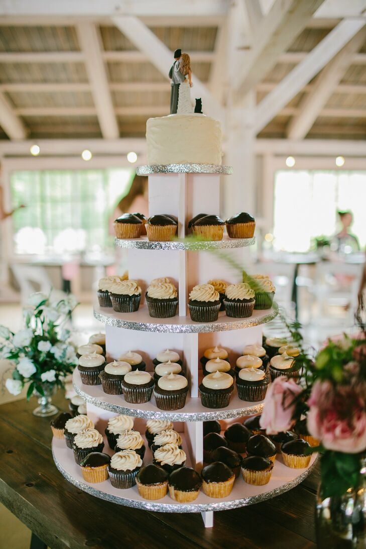 A variety of cupcakes were displayed on a handmade tower with a small cutting cake resting on top.